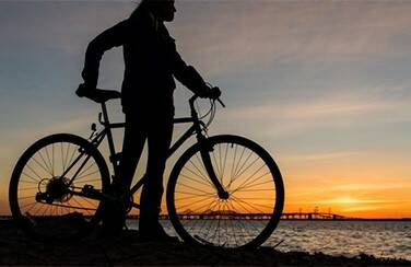 57437_woman riding bike by the bay